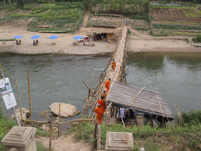 monks-walking-over-a-bamboo-bridge-tourists-have-to-pay-for-this